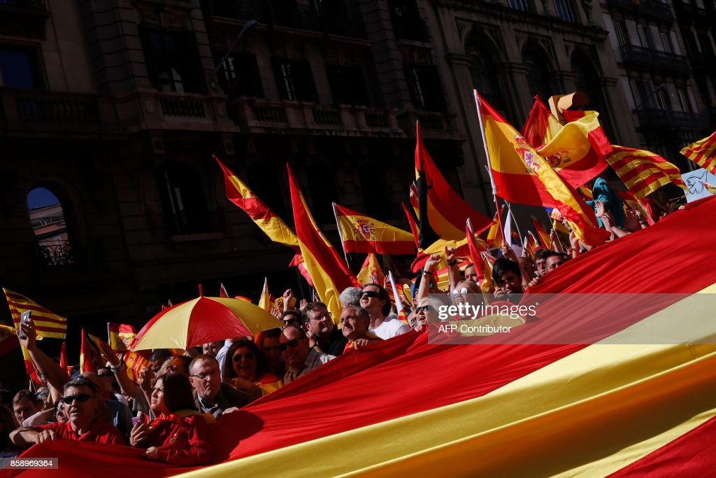 Protesters unfold a giant Spanish flag during a demonstration called by 'Societat Civil Catalana' (Catalan Civil Society) to support the unity of Spain on October 8, 2017 in Barcelona. The demonstration comes as Catalonia's separatist leaders have vowed to declare independence for the wealthy northeastern region of Spain following a banned secession referendum on October 1. BARRENA