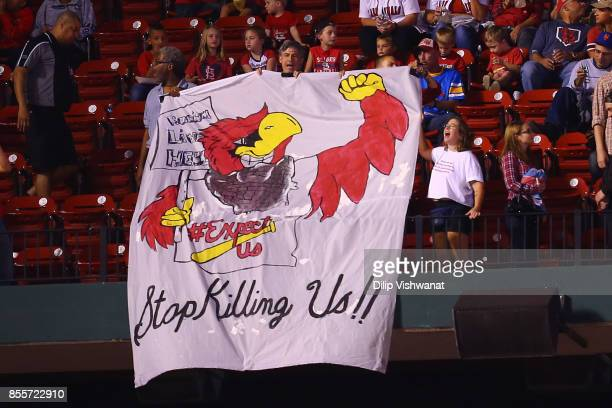 Protesters unfurl a banner during a game between the St. Louis Cardinals and the Milwaukee Brewers at Busch Stadium on September 29, 2017 in St....