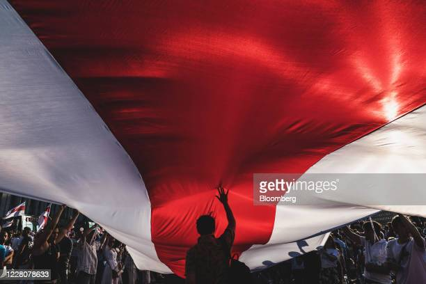 Protesters unfurl a banner in the colors of the former Belarus national flag as they call for the resignation of President Alexander Lukashenko in...