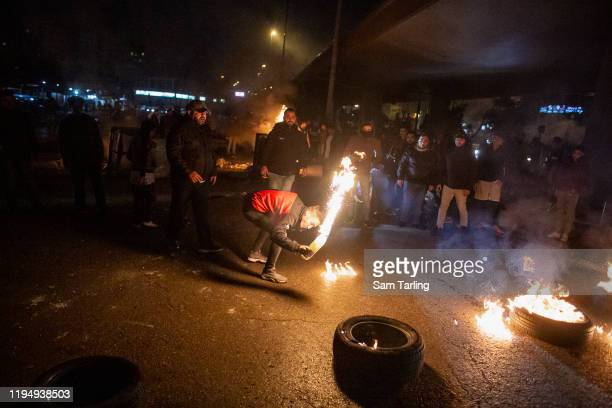 Protesters unhappy with the selection of Hezbollah backed Hassan Diab as the new Lebanese Prime Minister create a road block with burning tires, on...