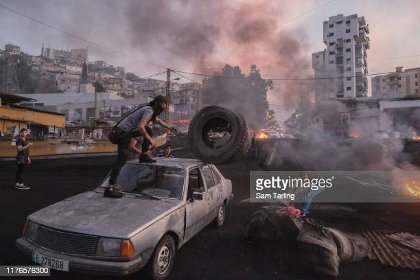 Protesters unload tyres from a car which they'll burn to block a highway in Beirut Lebanon during unrest sparked by economic difficulties on October...