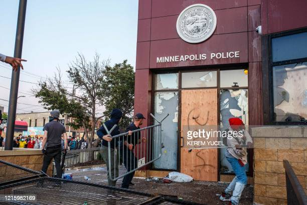 TOPSHOT Protesters use a barricade to try and break the windows of the Third Police Precinct on May 28 2020 in Minneapolis Minnesota during a protest...
