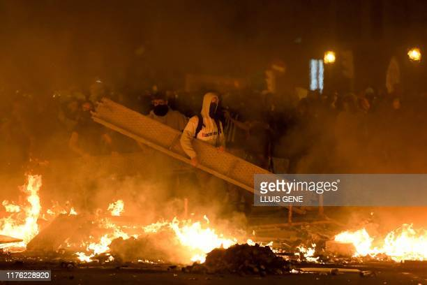 Protesters use a scaffold to make barricades during a demonstration called by the local Republic Defence Committees in Barcelona on October 16 after...