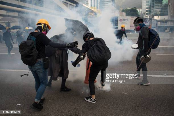 Protesters use a traffic cone to cover a tear gas canister during the demonstrations Despite the controversial extradition bill which originally...