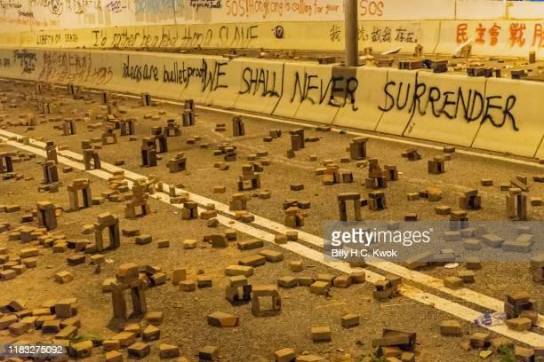 Protesters use bricks to barricade near Hong Kong Polytechnic University in the Tsim Sha Tsui district on November 18 2019 in Hong Kong China...