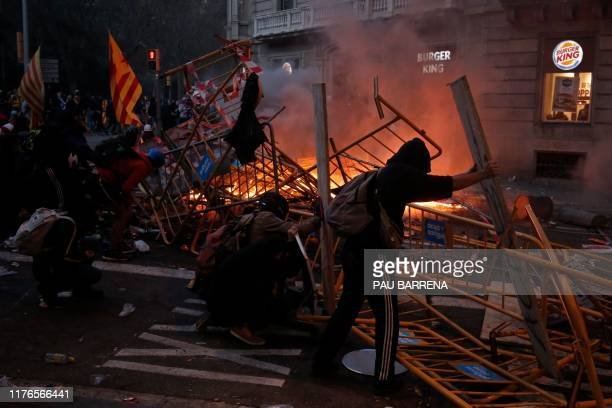 Protesters use fences as a barricade during clashes near the Police headquarters in Barcelona, on October 18 on the day that separatists have called...