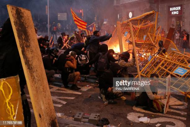 TOPSHOT Protesters use fences as a barricade during clashes near the Police headquarters in Barcelona on October 18 on the day that separatists have...