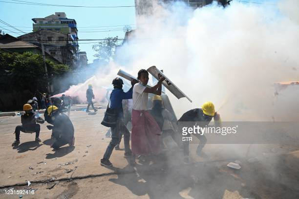 Protesters use fire extinguisher to create smoke cover against riot police during a demonstration against the military coup in Yangon on March 8,...