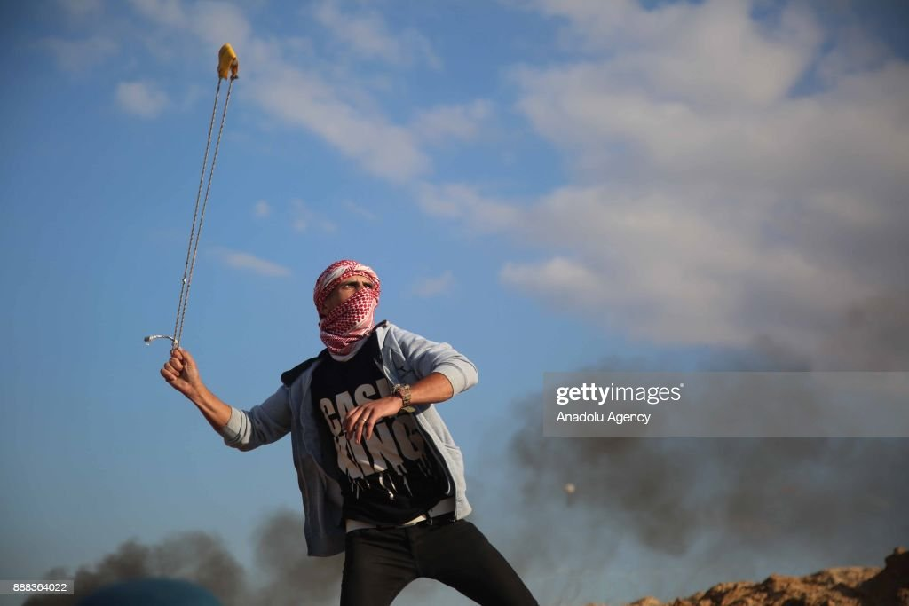 Protesters use slingshot to throw stone to Israeli security forces during a protest against the US President Donald Trumps recognition of Jerusalem as Israels capital, at Al Bureyc Refugee Camp in Israeli border, Gaza Strip, Gaza on December 8, 2017.
