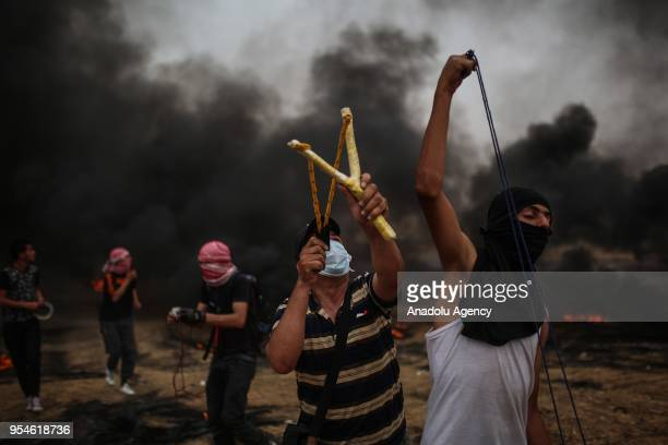 Protesters use slingshots to throw stones in response of Israeli soldiers' intervention during a protest in support of Great March of Return near...