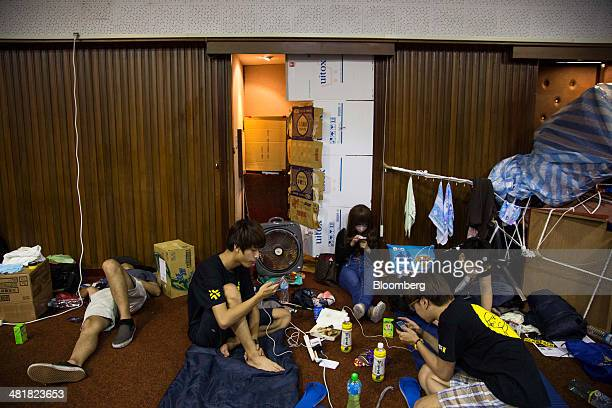Protesters use their mobile phones while sitting inside Taiwan's legislative chamber as the occupation enters its 14th day in Taipei Taiwan on Monday...