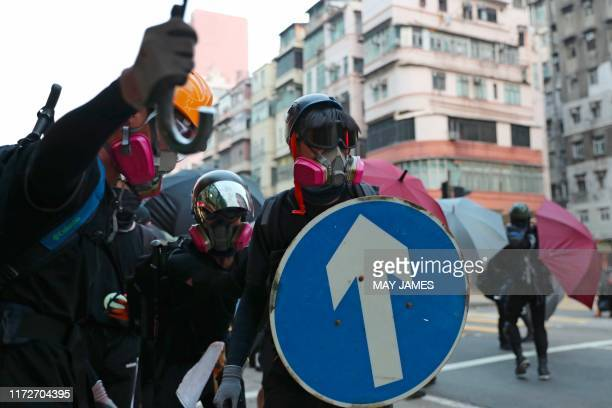 Protesters use umbrellas and a street sign for cover as they stand off with police during a demonstration in the Sham Shui Po area in Hong Kong on...