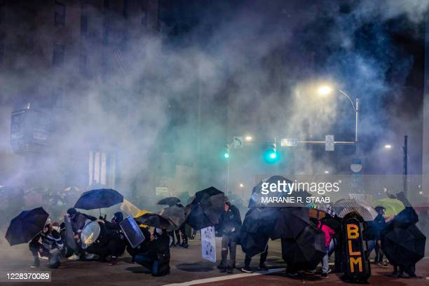 """Protesters use umbrellas and homemade shields in an attempt to protect themselves from pepper,""""less-lethal"""" munitions and teargas in Rochester, New..."""