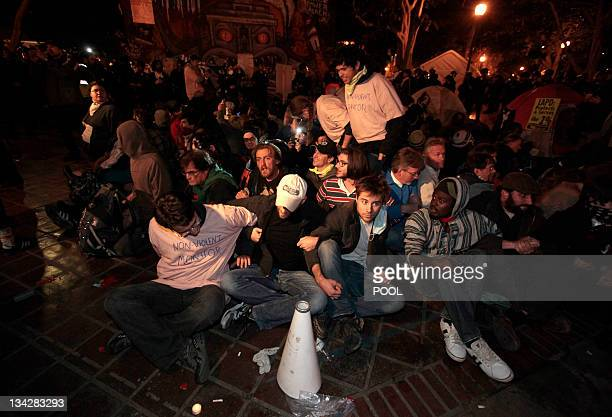 Protesters wait to be arrested at the Occupy LA encampment outside City Hall in Los Angeles November 30 2011 The nearly twomonthold encampment is...