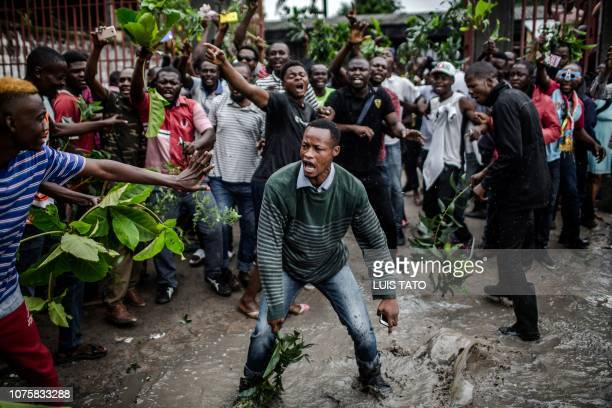 TOPSHOT Protesters waiting to cast their ballot demonstrate outside the College St Raphael polling station in Kinshasa on December 30 2018 while...
