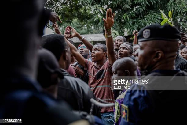 Protesters waiting to cast their ballot demonstrate outside the College St Raphael polling station in Kinshasa on December 30 2018 while Democratic...