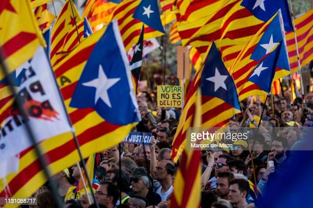 Protesters waiving Catalan independence flags during a demonstration under the slogan 'Self-determination is not a crime'. In the center a placard...