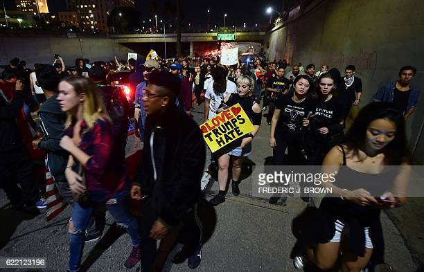 Protesters walk back up a freeway onramp amid a chaotic traffic situation with the shutdown of the freeway in downtown Los Angeles California after...