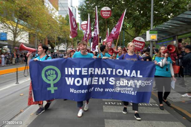 Protesters walk behind a banner as they march along Swanston Street during a rally on International Women's Day in Melbourne Australia on Friday...