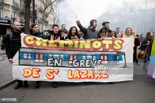 Protesters walk behind a banner during a protest march by railway workers and other labor union members in Paris France on Tuesday April 3 2018...