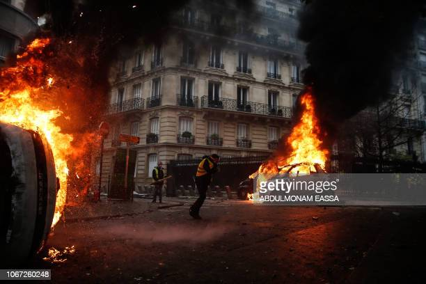 TOPSHOT Protesters walk by burning cars during clashes with riot police on the sideline of a protest of Yellow vests against rising oil prices and...