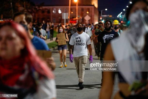 Protesters walk during a demonstration against the shooting of Jacob Blake in Kenosha, Wisconsin on August 26, 2020. - Outrage continued to spread...