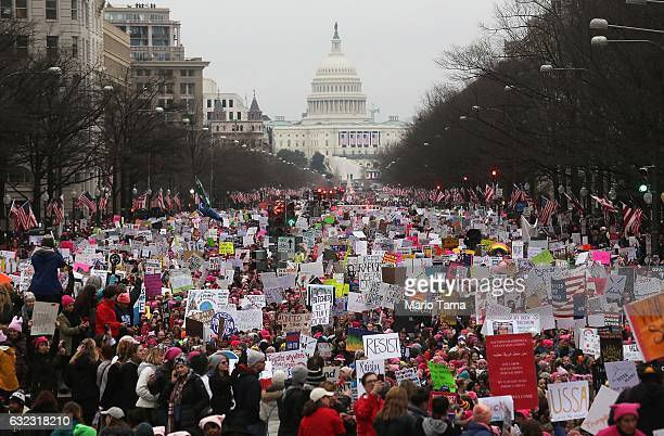 Protesters walk during the WomenÕs March on Washington, with the U.S. Capitol in the background, on January 21, 2017 in Washington, DC. Large crowds...