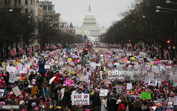 Protesters walk during the Women's March on Washington with the US Capitol in the background on January 21 2017 in Washington DC Large crowds are...