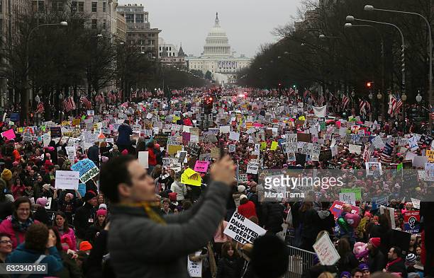 Protesters walk during the Women's March on Washington, with the U.S. Capitol in the background, on January 21, 2017 in Washington, DC. Large crowds...