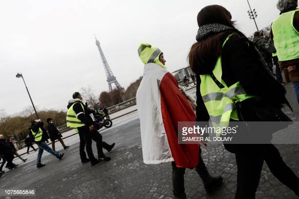 Protesters walk in a street with the Eiffel Tower on the background during a demonstration called by the yellow vests movement, to protest against...