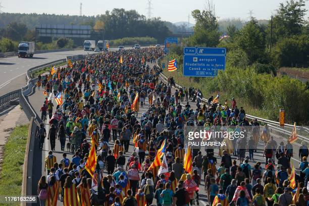 Protesters walk on the AP-7 highway near Girona, on October 16 a day after police arrested 51 people across Catalonia overnight after violent...