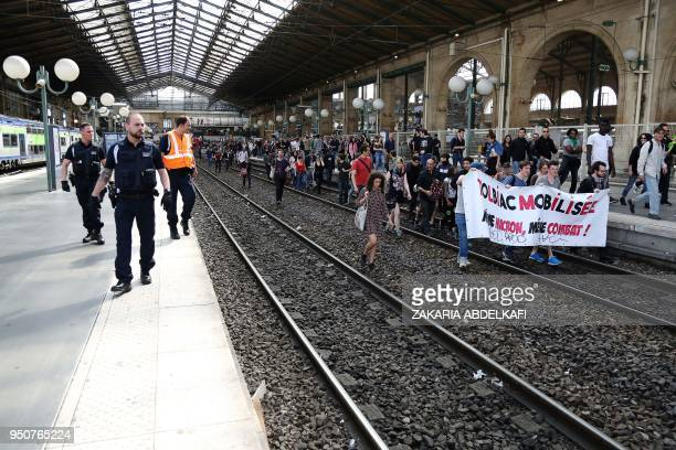 Protesters walk on the tracks as they take part in an unofficial demonstration against the French Government's plans to overhaul the stateowned rail...