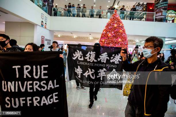 TOPSHOT Protesters walk past a Christmas tree as they march through the Harbour City shopping mall in the Tsim Sha Tsui district of Hong Kong on...