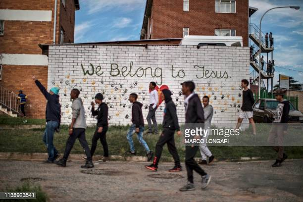 TOPSHOT Protesters walk past a graffiti on a wall in the streets of Johannesburg on April 23 2019 during a protest against the lack of service...