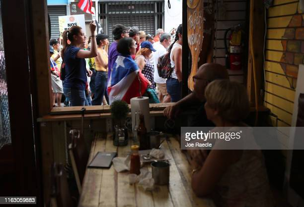 Protesters walk past a restaurant as they demonstrate against Ricardo Rossello the Governor of Puerto Rico on July 19 2019 in Old San Juan Puerto...