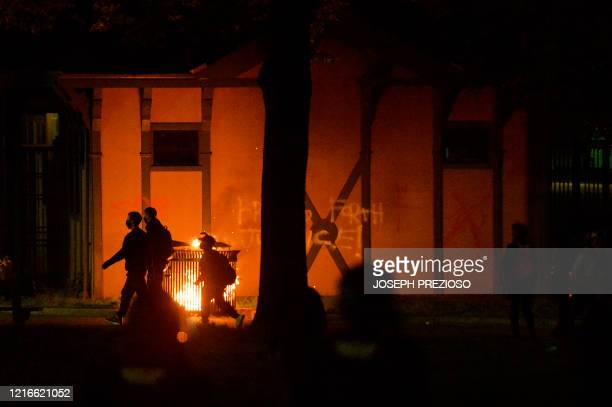 Protesters walk past a small fire during clashes with police after a demonstration over the death of George Floyd an unarmed black man who died in...
