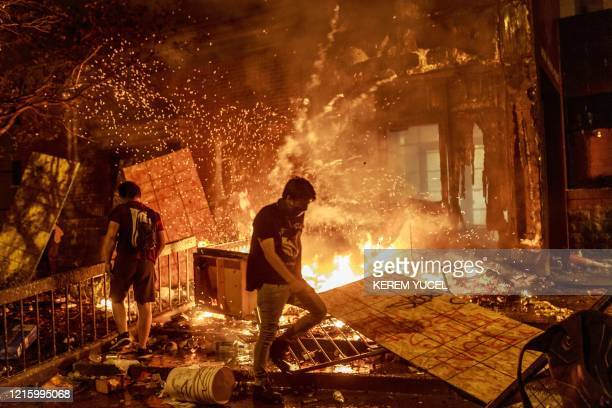 TOPSHOT Protesters walk past burning debris outside the Third Police Precinct on May 28 2020 in Minneapolis Minnesota during a protest over the death...