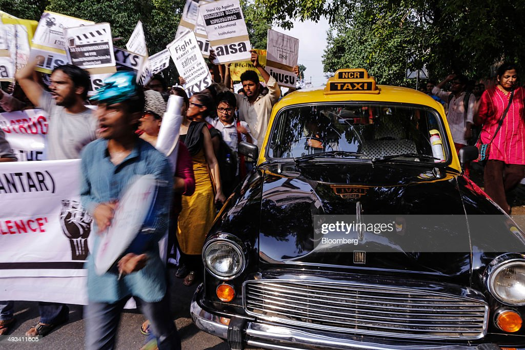 Protesters walk past taxi driver Gurmeet Singh as he sits inside a Hindustan Motors Ltd. Ambassador taxi in New Delhi, India, on Saturday, Sept. 19, 2015. As cabs lured by app-based platforms proliferate in India, where car ownership is low and public transportation services in most cities and towns havent kept pace with the needs of a growing population, drivers are facing stiffer competition for rides. Photographer: Dhiraj Singh/Bloomberg via Getty Images