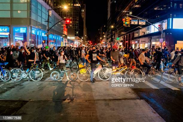 Protesters walk their bikes and march through the streets after a judge announced the charges brought by a grand jury against Detective Brett...