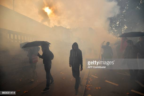 Protesters walk through tear gas as they take part in a demonstration called by the General Confederation of Labour French worker's union outside the...