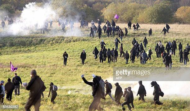 Protesters walk through tear gas fired by Danish police in a bid to break through police cordons and tear down a fence on October 25 2008 at the...