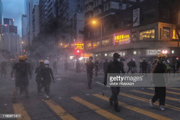 Protesters walk through tear gas fired by riot police during a standoff in the Wan Chai district in Hong Kong on August 11 2019 Thousands of...