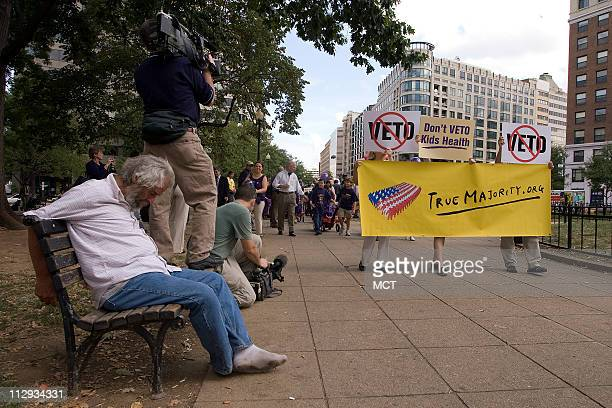 Protesters walk to the White House to the White House to deliver red wagons carrying mail bags filled with petitions signed by more than 1 million...