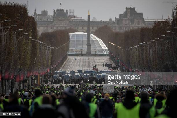 Protesters walk towards a police line on the ChampsElysées during the 'yellow vests' demonstration on December 8 2018 in Paris France ''Yellow Vests'...