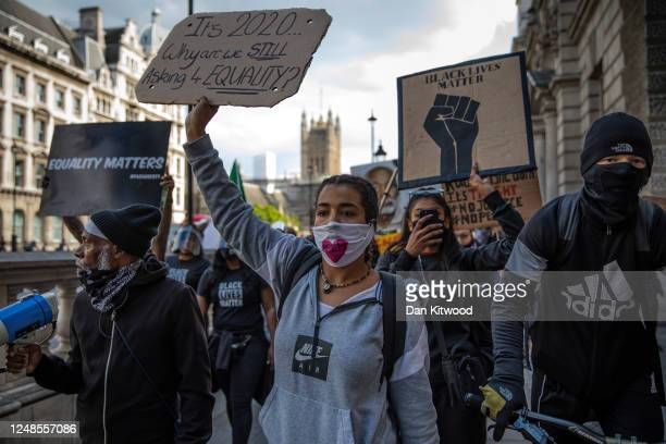 Protesters walk up Downing Street after gathering in Parliament Square to commemorate the life of George Floyd at 5pm, the time when his body will be...