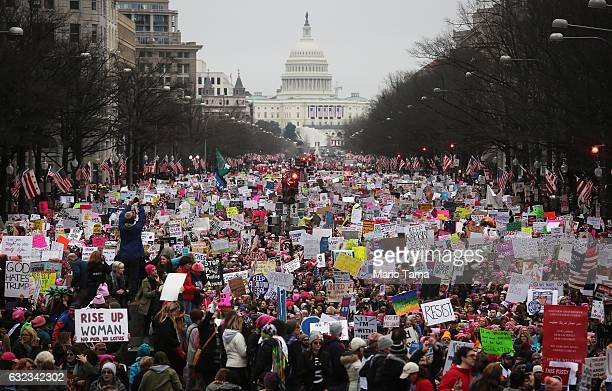 Protesters walk up Pennsylvania Avenue during the Women's March on Washington with the US Capitol in the background on January 21 2017 in Washington...