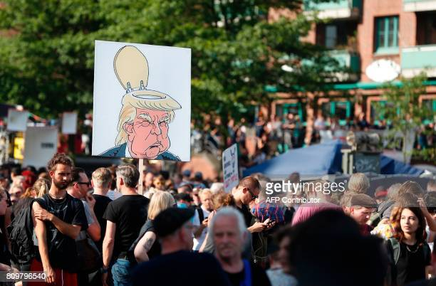 Protesters walk with a placard featuring US president Donald Trump with a toilet seat as part of his head during the 'Welcome to Hell' rally against...