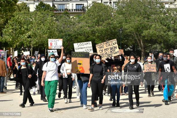 Protesters walk with anti racism signs during a demonstration against racism and police brutality in front of the Eiffel Tower on June 06 2020 in...