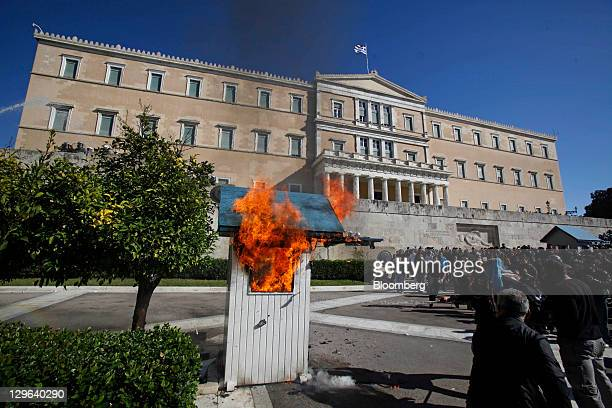 Protesters watch a sentry box burn outside the Greek parliament during a day of demonstrations against austerity cuts in central Athens Greece on...