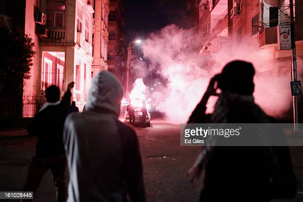 Protesters watch as other demonstrators fire fireworks toward nearby Egyptian riot police during violent protests at the Presidential Palace in...